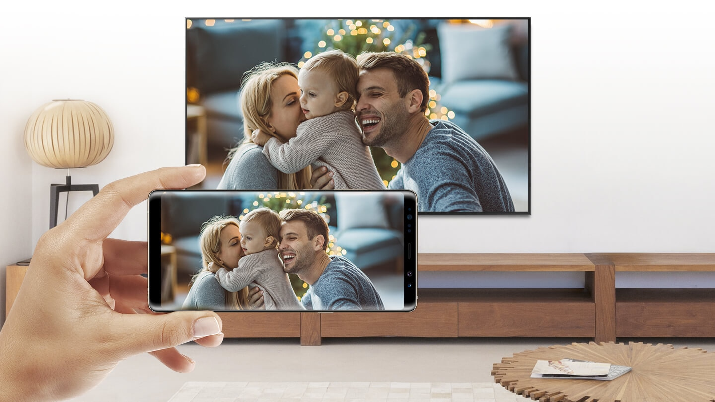 Mobile Phone and Smart TV sharing a same screen; photo of parents and a child.