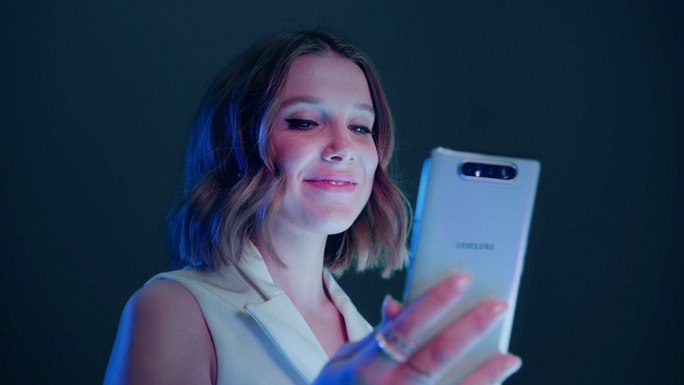 Millie Bobby Brown sonríe mientras mira un Galaxy A80 color ghost white en su mano