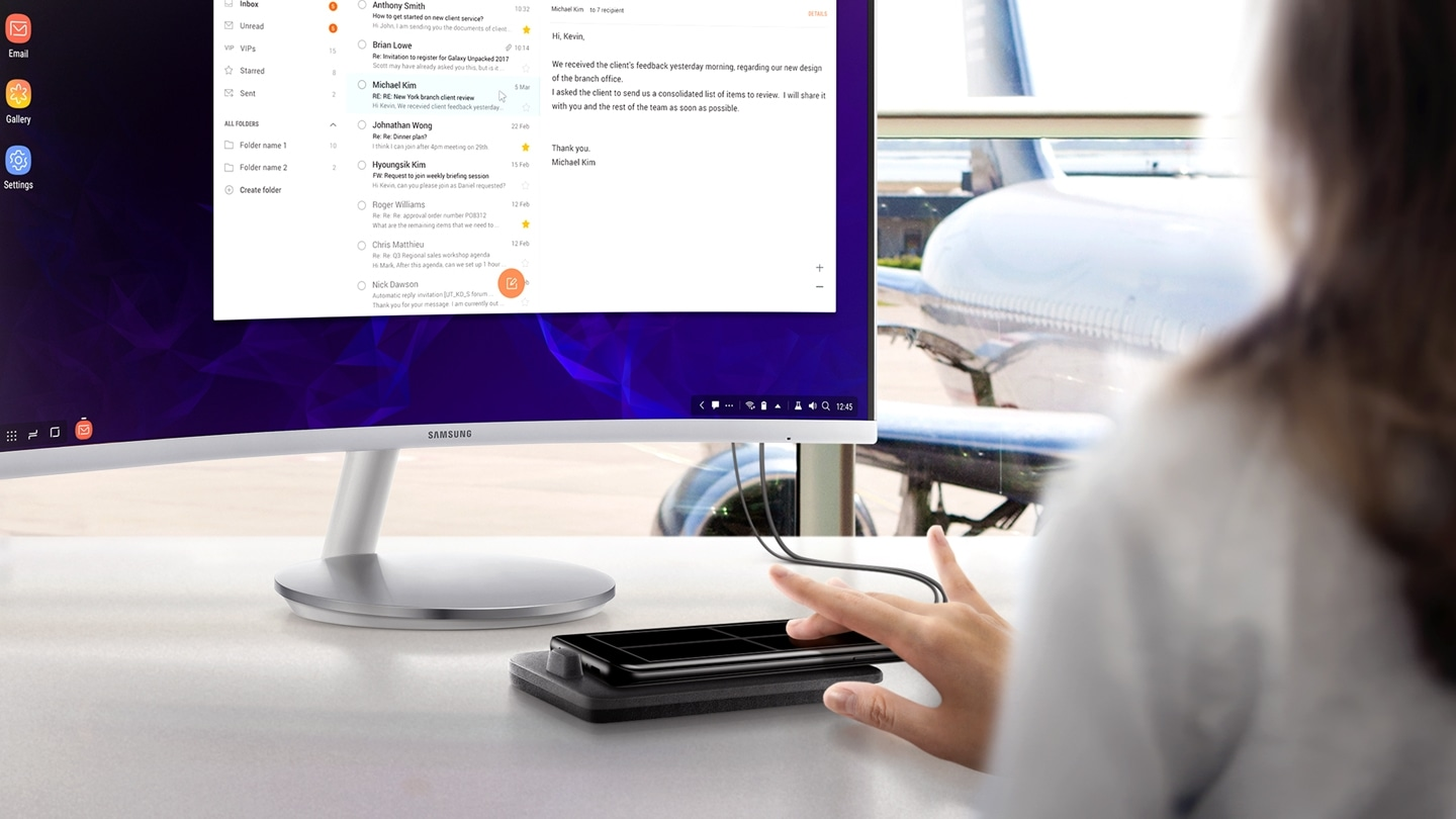 Image of person working at a desk with Galaxy S9 or S9+ and Samsung DeX Pad connected to a Samsung monitor