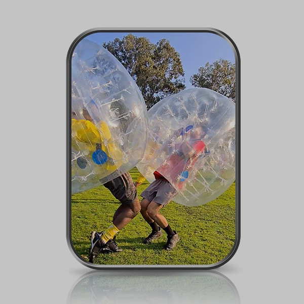 Two men are colliding on an outdoor soccer field in inflatable bubble bumper suits. Their knees are slightly bent.