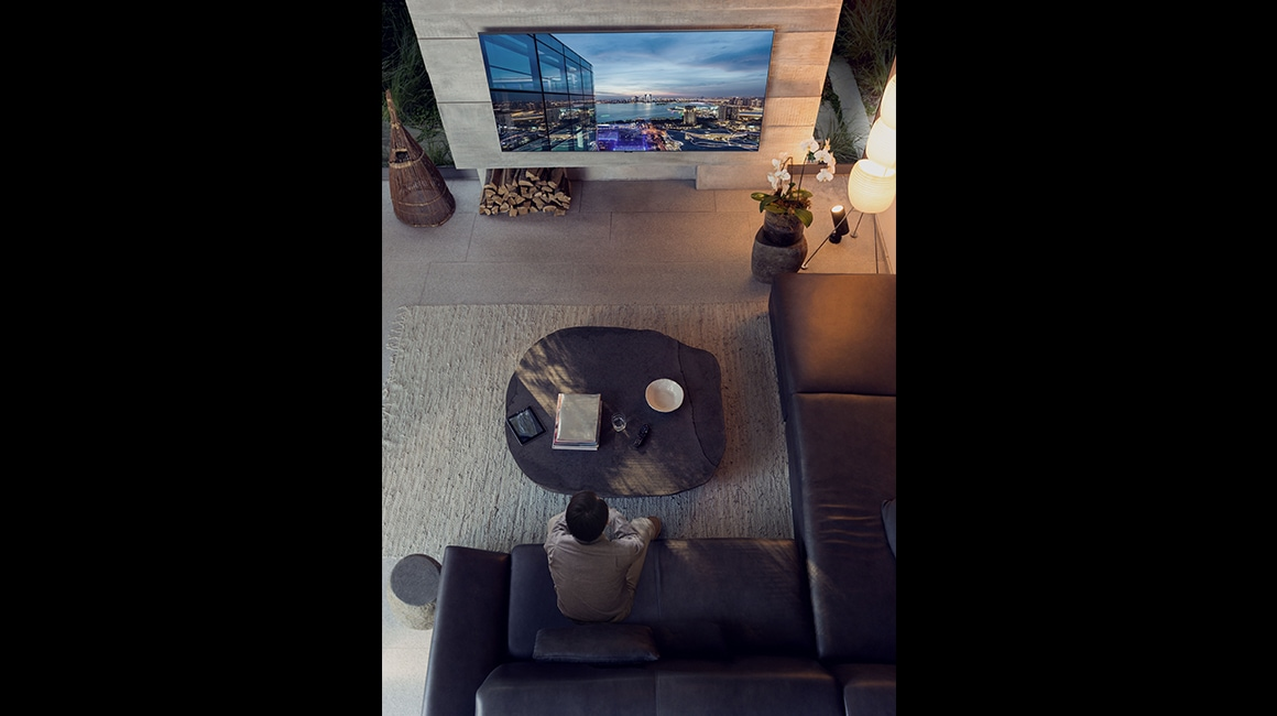 Bird's Eye view of grey-toned cozy living room. A man is sitting on a couch and watching a city's beautiful night view on the Super Big TV screen.