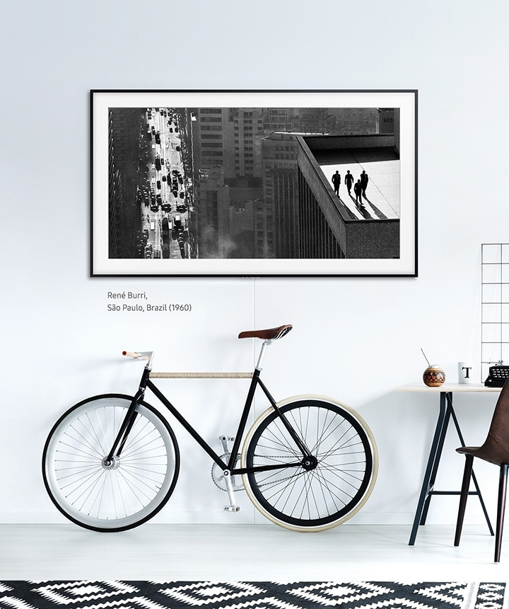 The Frame hanging on a wall above a bicycle and desk with the basic charcoal black frame.