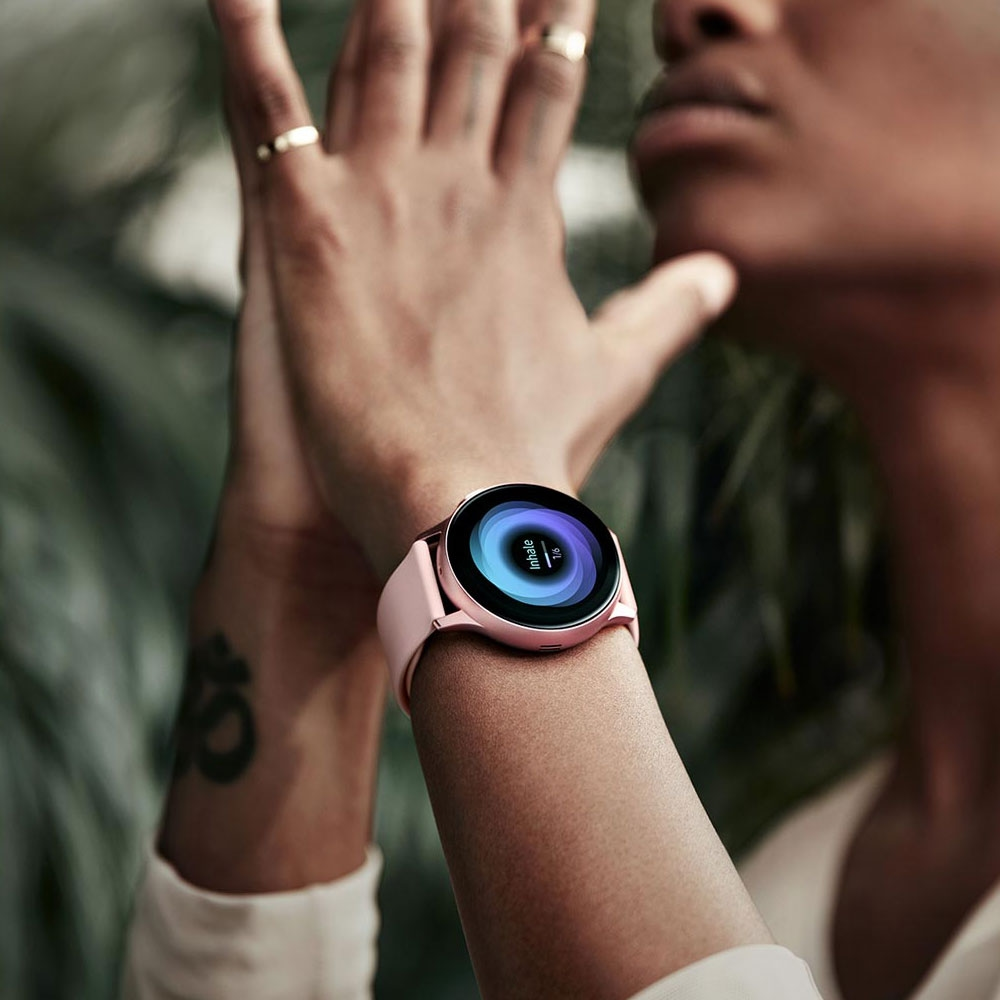 A woman practicing yoga with hands together and a Galaxy Watch active2 in Pink Gold on her wrist that displays breathing exercises on the watch GUI, after which a separate person is shown sleeping with a Galaxy Watch active2 on the wrist that tracks sleeping patterns and compares them to others in the same age bracket as displayed on the watch GUI.