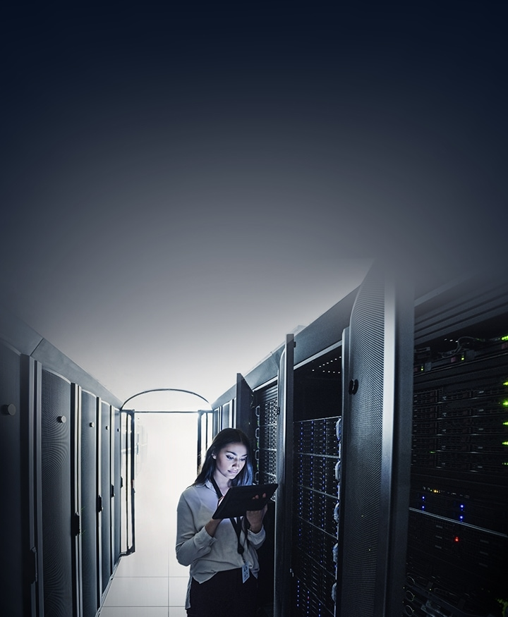 A woman is looking at the laptop on his hand in the server room