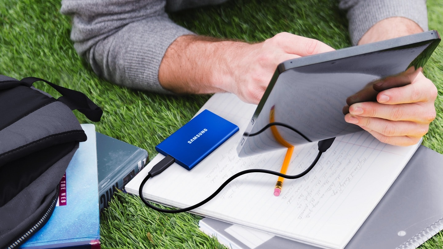 A lifestyle image of a man lying on the grass using a Portable SSD T7 product.