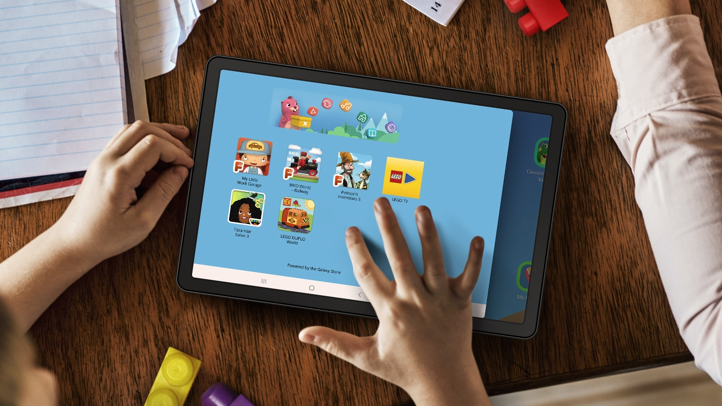 A tablet on a table surrounded by papers and LEGO blocks. A child's hands are nearby and their right hand is touching the tablet screen. Onscreen is the LEGO App UI, showing different kinds of entertainment your child can experience.