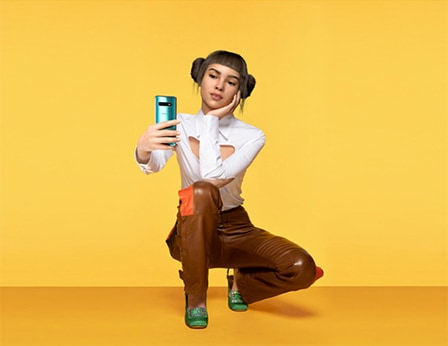 Closeup shot of Lil Miquela against a pale yellow background as she squats down, holding a reflective blue Samsung Galaxy S10 smartphone