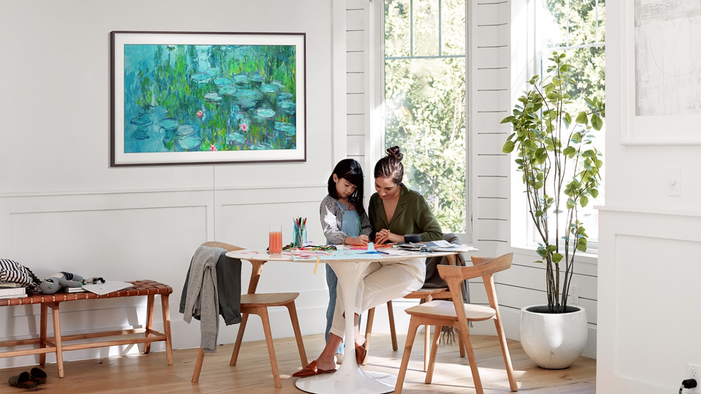 The Frame with a black bezel is mounted stylishly on a white wood wall in a kitchen. Onscreen is an image of water lilies on a wall and in the foreground a mother and daughter are drawing something at a table.