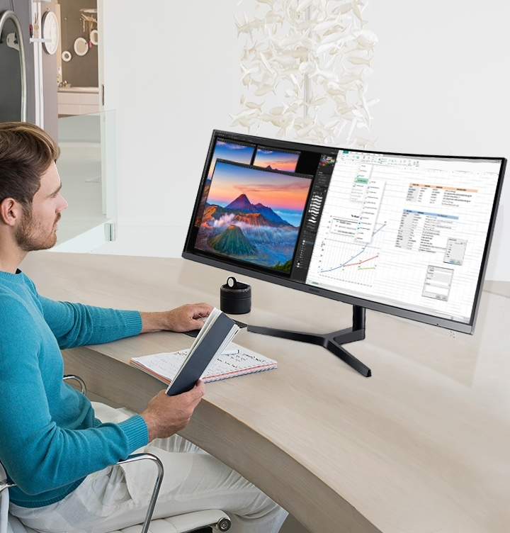 There is a table in the office, and you can see the man holding the mouse and book while he is looking at the segmented work screen.
