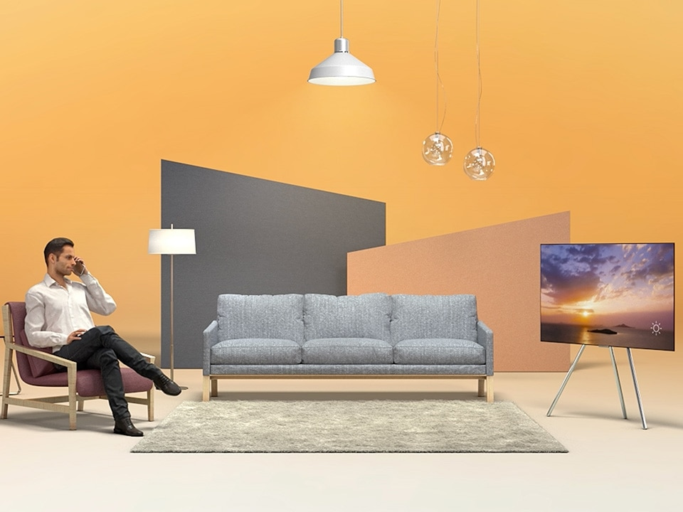 The man sitting on a sofa in his living room, talking to his girlfriend while watching TV.