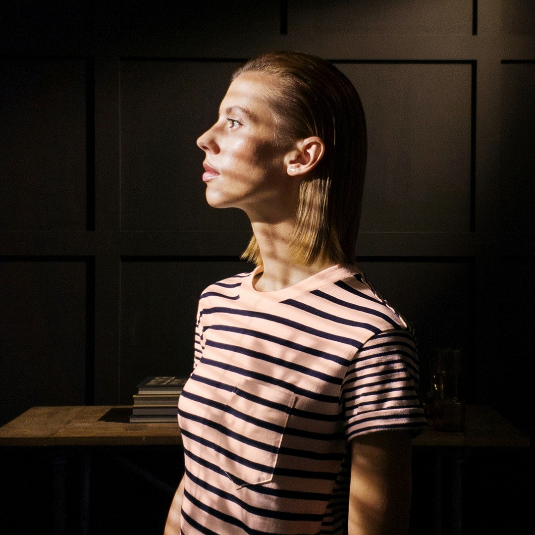 A photo taken by Galaxy Note9 of a woman wearing a striped shirt and covered in striped shadows