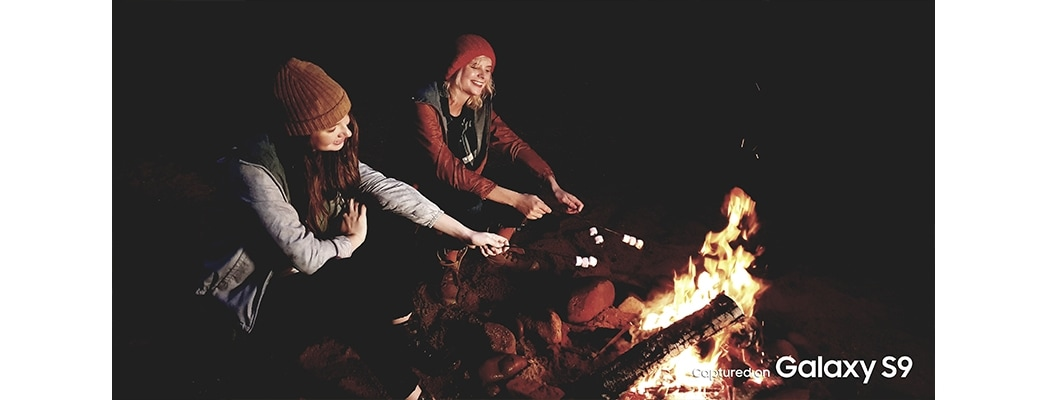 two girls in front of the bonfire