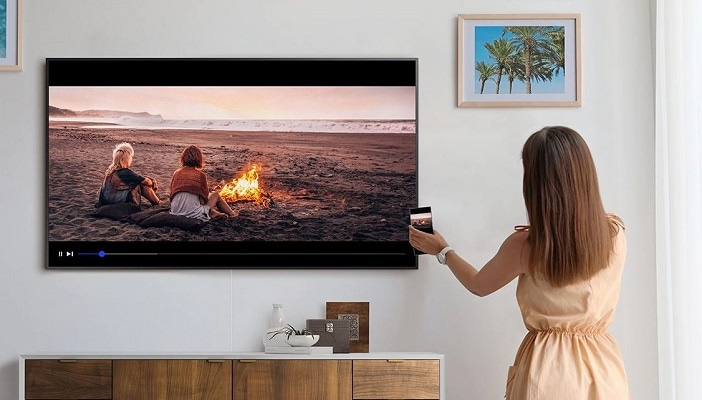 a woman tapping phone on the tv