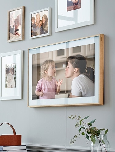 The Frame TV on the wall displaying a family photo among other picture frames.
