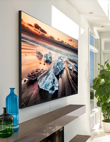 A lifestyle image of the 2019 new Samsung QLED Q900R. Image shows the side view of Q900R mounted on a wall over the fire place in the living room.