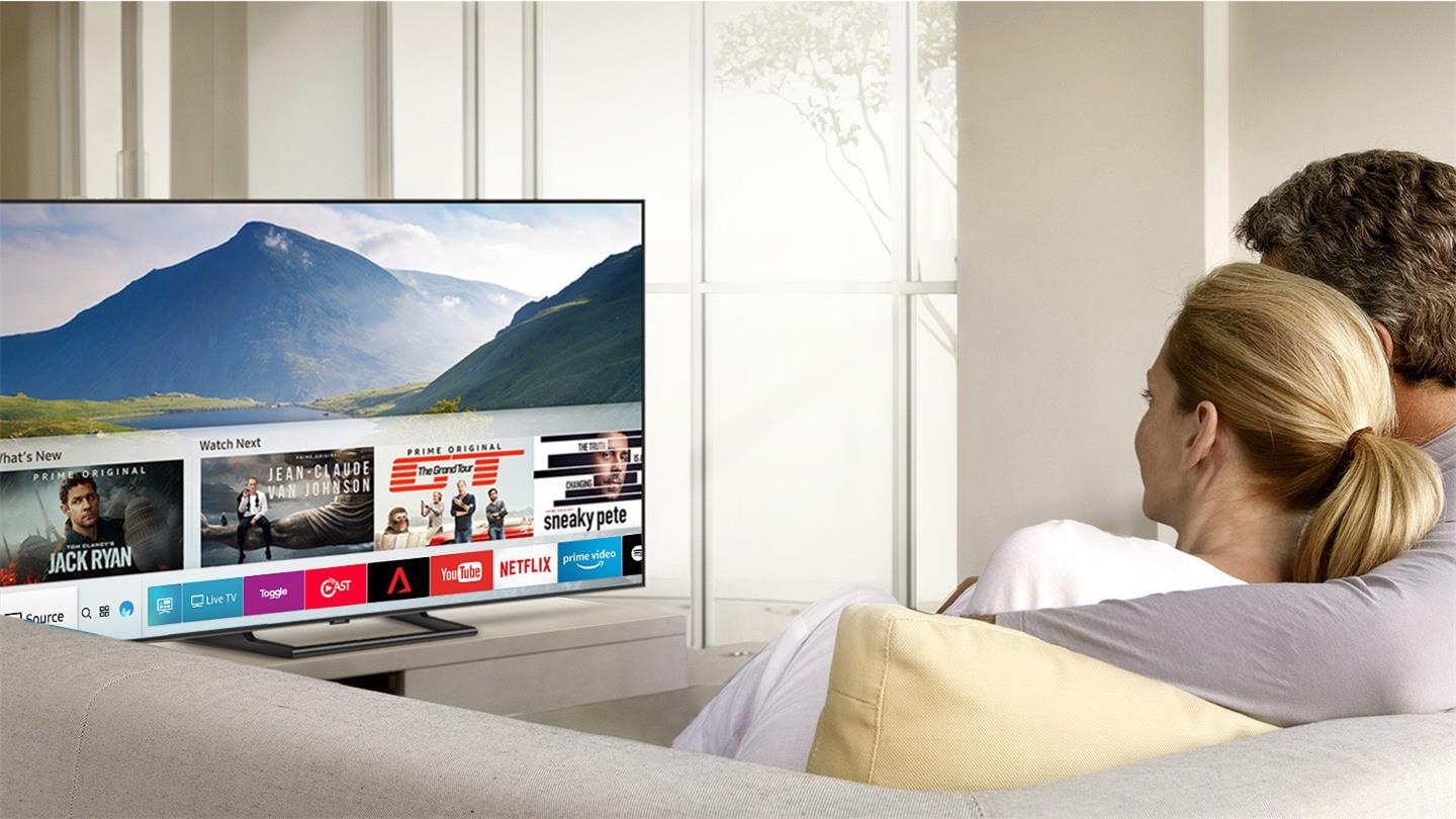 2 people are watching Smart TV and Smart Hub UI is displayed over a nature background image on TV screen; The UI contains various content, such as, 'What's New', 'Watch Next', and several applications like Netflix, Amazon Prime Video, YouTube, Facebook Video, Google Play Movies & TV, SmartThings, Gallery, Internet.