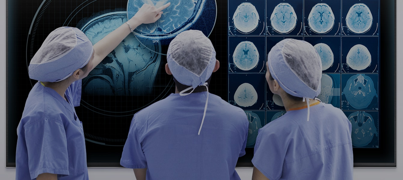 A group of doctors analyzing a CT image on a Samsung SMART Signage TV