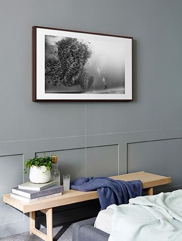 The Frame with the Invisible Connection on the wall above a bench opposite the bed in bedroom.