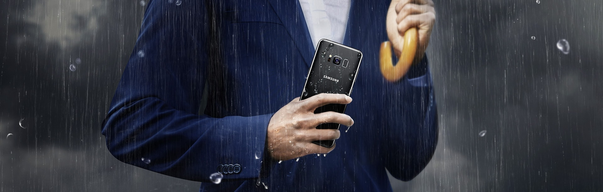 Man in business suit holding the Galaxy S8 in the rain