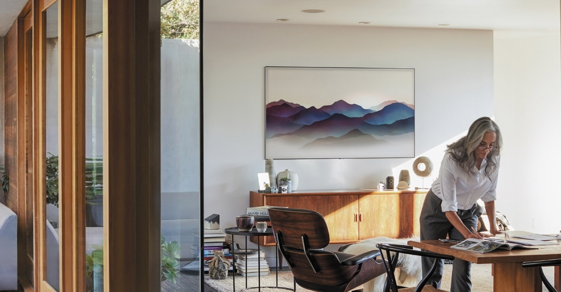 A lifestyle image of the 2018 new QLED TV Q9F. Image shows QLED TV is mounted on wall with Ambient Mode in a sunny room, and a woman is working naturally.