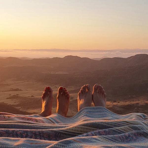 A photo taken by Galaxy Note9 of two pairs of feet peeking out from under a blanket in the sunset, appearing to hang off a cliff
