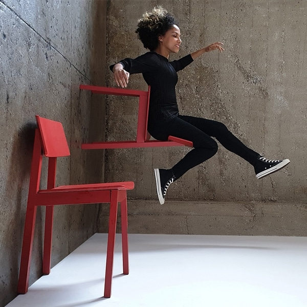 A photo taken by Galaxy Note9 of a woman wearing all black, sitting in a red chair that appears to be standing on the wall