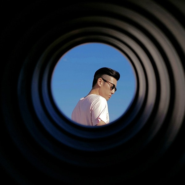 A photo taken by Galaxy Note9 of a man wearing sunglasses, seen through a round tube