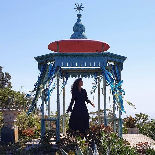 A photo taken by Galaxy Note9 of a woman wearing a long dress, standing in a blue and red gazebo surrounded by greenery