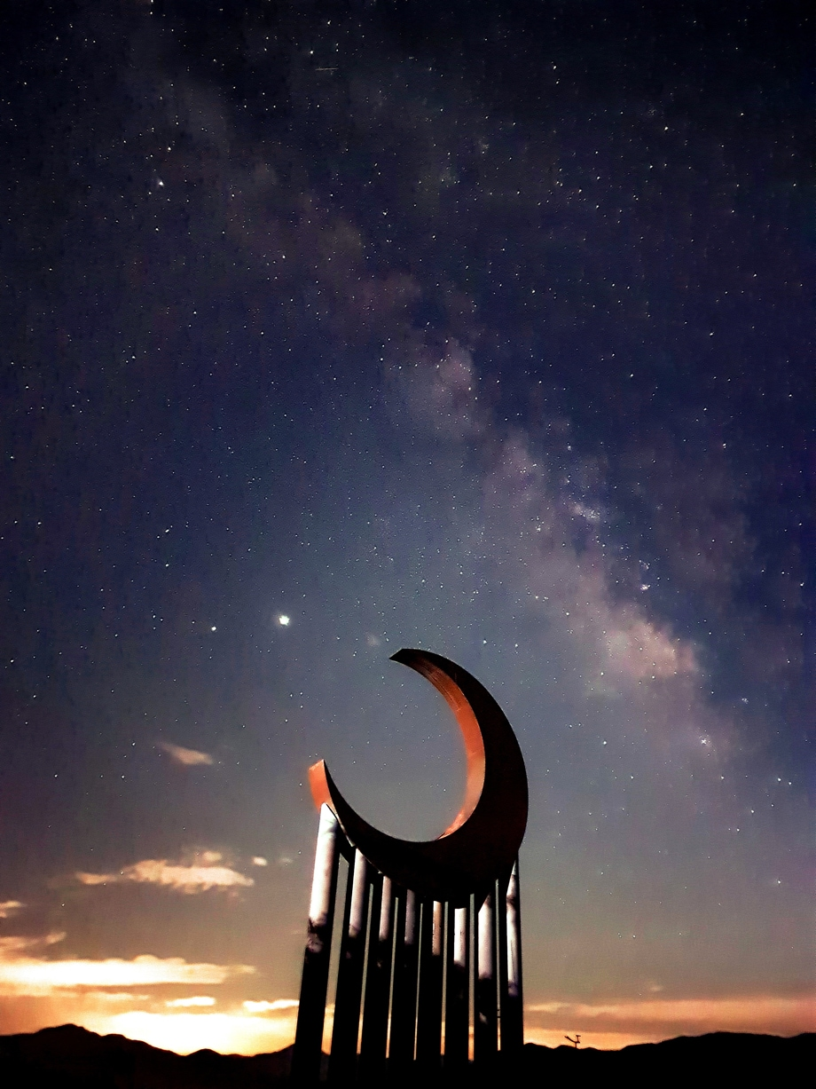 Sculpture of a moon, supported by columns against a starry night sky during sunset