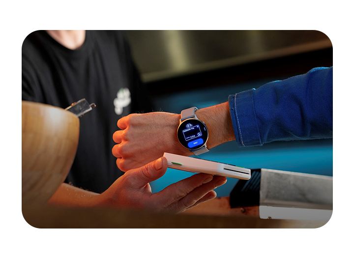 A man's wrist is shown wearing a Galaxy smartwatch using Samsung Pay to contactless pay at a food truck.