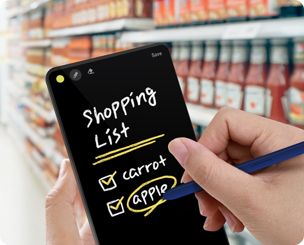 "A closeup view shows a person in a supermarket holding a phone and S Pen. The phone screen shows the handwritten text ""Shopping List"" and a checklist with the items ""carrot"" and ""apple""."