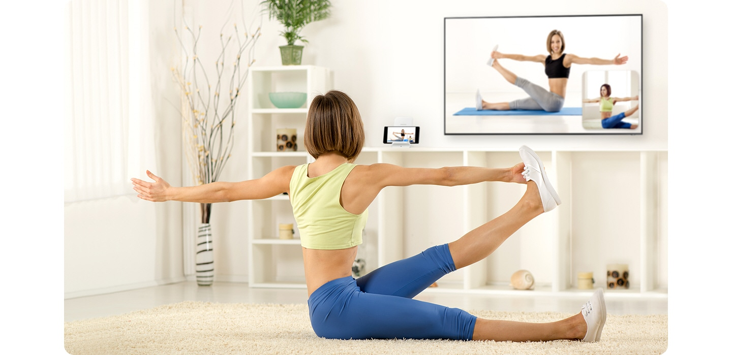 A woman, sitting down in her living room, is following a yoga pose showing on the TV in front of her. Next to the TV, her smartphone is recording her pose, which is being mirrored onto a small window on the lower righthand corner of her TV so that she can compare her pose to the instructional video playing.