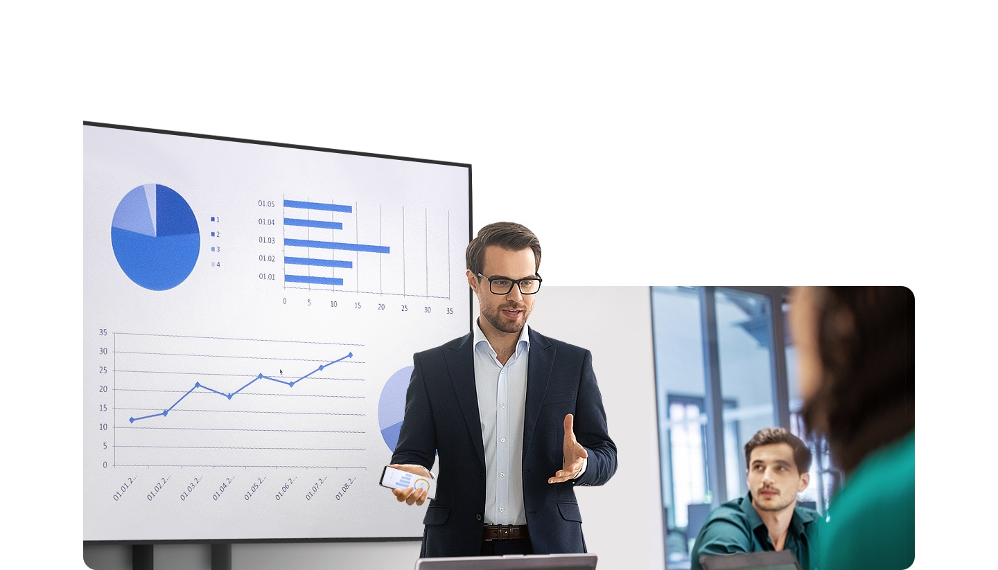 A man is giving a presentation in front of people in an office. Behind him, a large display is showing various graphs and he is holding his Galaxy in his hand.