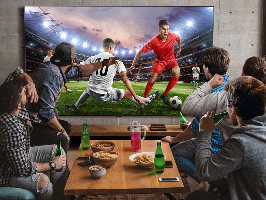 5 men sitting around a mini table with snacks and beverages are watching football game on the large screen TV. Super Big TV is the best big screen TV for sports.