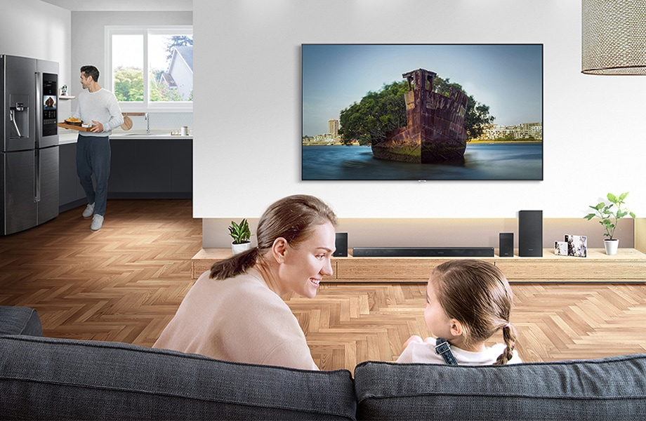 A mother and daughter watch a movie on the big screen TV in the living room, while the father is seen in the background grabbing snacks from the kitchen and watching the same movie through the mirrored feed on the Family Hub screen.
