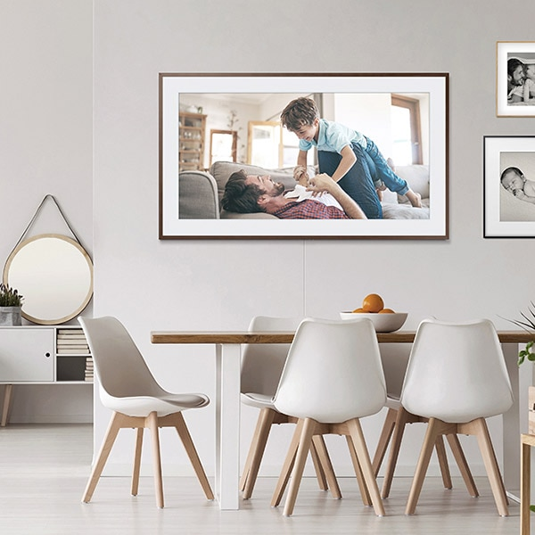 The Frame displaying a family photo hangs on a wall in a room with a table and five chairs.