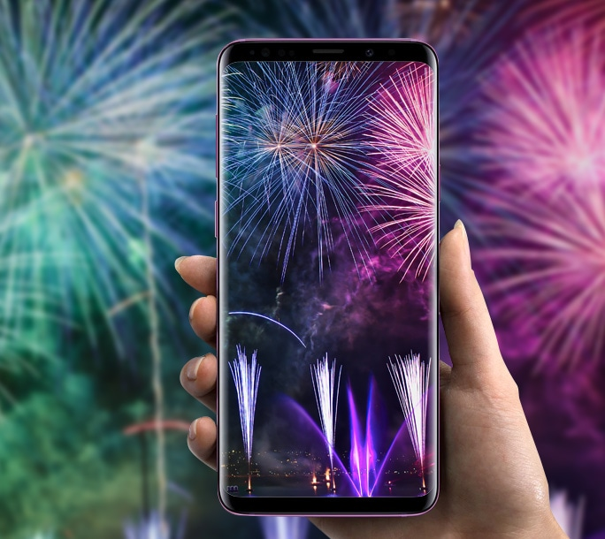 5.	The Samsung Galaxy S9 being held up to take photos of fireworks that are in the background