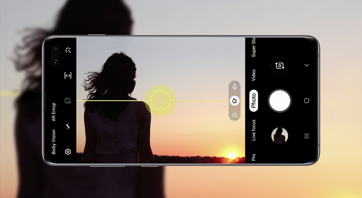 A smartphone taking a picture of a woman and sunset