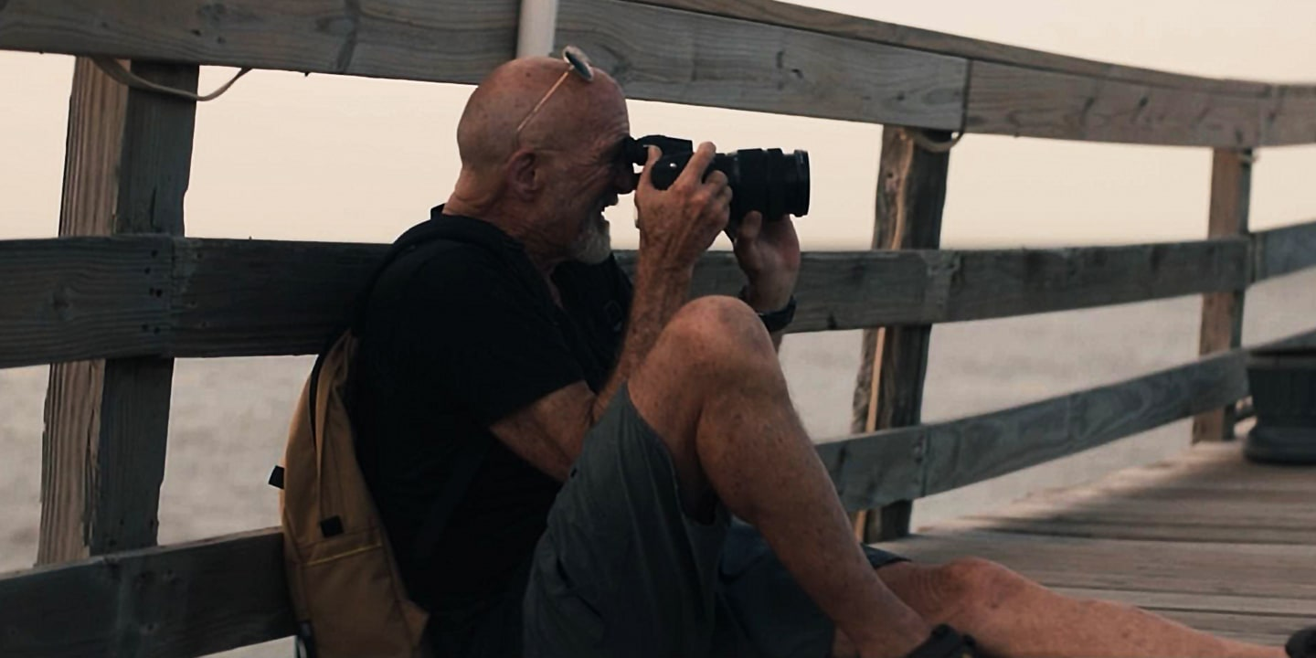 David Alan Harvey, a photographer of Magnum Photos, is taking a picture sitting on a wooden bridge