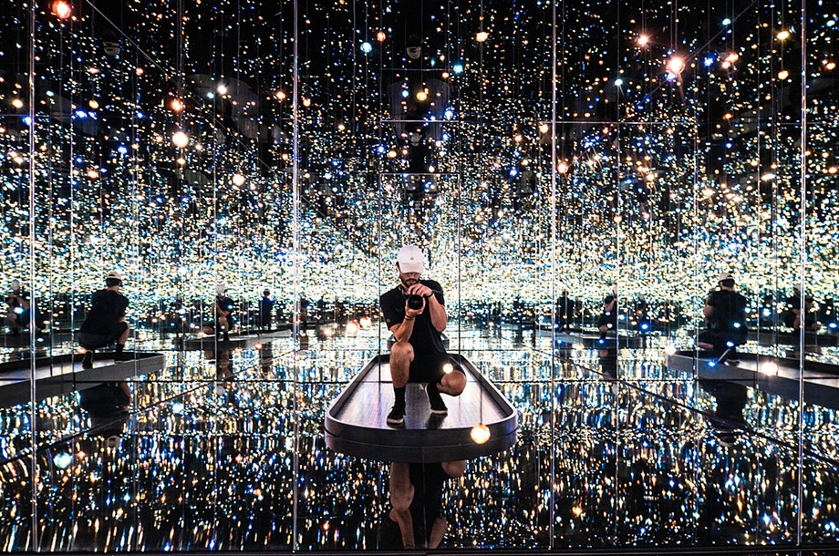 Photo of man crouched down taking an infinity photo in many mirror