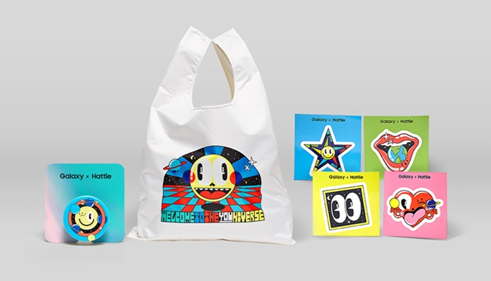 A white canvas bag and various other goods featuring colorful designs from a collaborating artist.