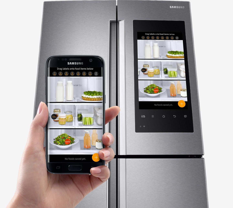 Ruce držící chytrý telefon a rodinné rozbočovače Obrázek produktu s zavřenými dveřmi.  Jídlo uvnitř je zobrazeno na obrazovce mobilního i rodinného rozbočovače.