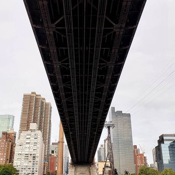 A photo taken by Galaxy Note9 of city buildings, with the dark underside of a bridge cutting through the center of the photo