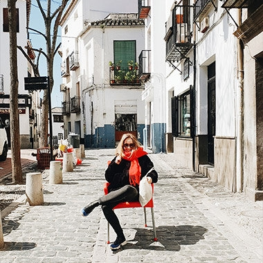 A photo captured with Galaxy by Instagram user @inescostamonteiro of a woman sitting on a red chair in the middle of a sidewalk