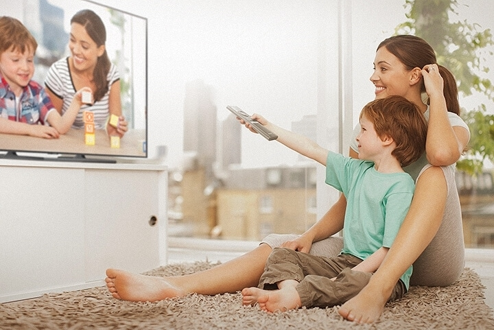 Mother and child enjoying old memories on the TV