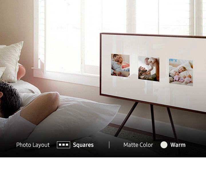 The Frame TV is displaying three photographs in a square, 3-part layout. It has a walnut bezel and is mounted on a studio stand in a bedroom.