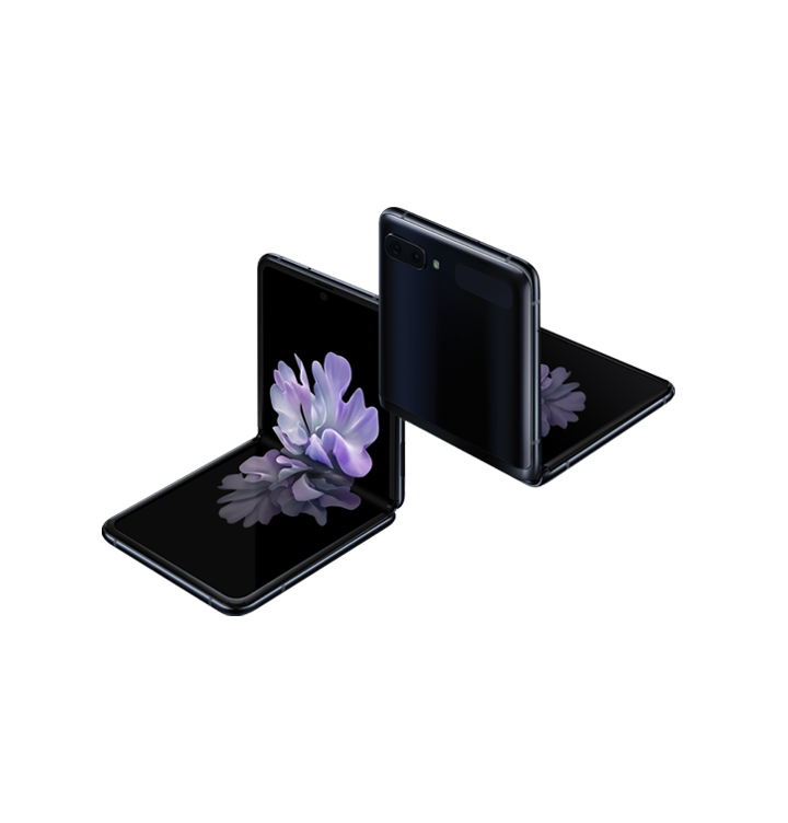 Two Galaxy Z Flip phones in Mirror Black at a three-quarter angle, one seen from the front and one seen from the rear. Both are folded at right angles with freestop folding. The one seen from the front has the blossoming flower wallpaper onscreen