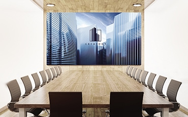 The Wall mounted at the front center of a bright, corporate meeting room showing a corporate logo.