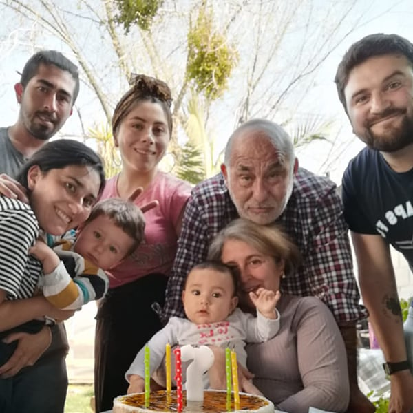 Family gathered around the table smiling while celebrating youngest child's birthday