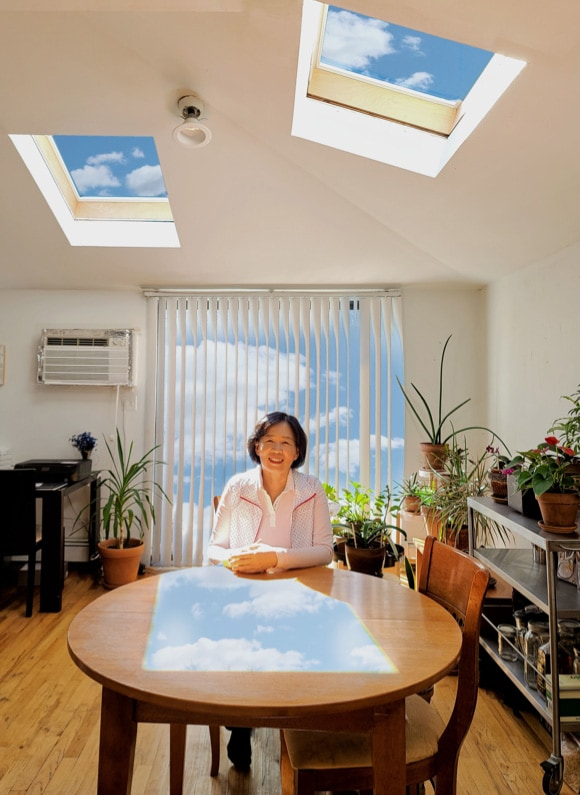 Woman sitting at a table in a room with windows and plants.